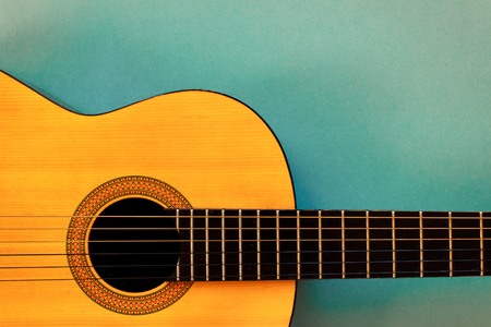 Photo pour Acoustic classic guitar on blue background. Simple musical instrument with copy space - image libre de droit