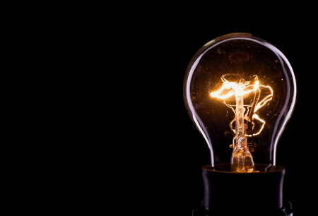 Photo pour Horizontal photo of a bulb on black background. Only outline of a glass bulb is visible and inner part with lighted wire is there. - image libre de droit