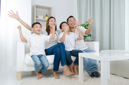 Photo pour Asian family watching television and shouting on their home side in a sporting competition - image libre de droit