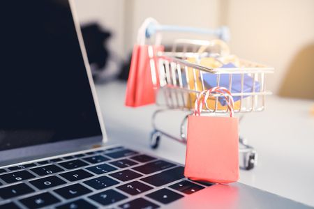 Photo pour Shoping online concept, Colorful paper shopping bag in trolley on laptop. Customer can buy everthing from office or home and the messenger will deliver. - image libre de droit