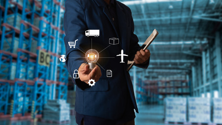 Foto de Business Logistics concept, Businessman manager touching icon for logistics on Modern Trade warehouse background. Industry 4.0 concept - Imagen libre de derechos