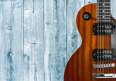 Foto de Part of the orange electric guitar on wooden background. A place for writing of the text - Imagen libre de derechos