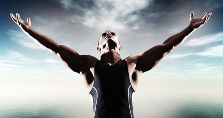 Foto de Muscled fitness triathlon athlete. Arms spread wide. Victory. Standing near lake. - Imagen libre de derechos