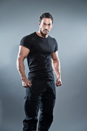 Photo for Combat muscled fitness man wearing black shirt and pants. Studio shot against grey. - Royalty Free Image