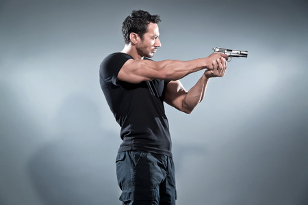 Photo pour Action hero muscled man shooting with gun. Wearing black t-shirt and pants. Studio shot against grey. - image libre de droit