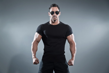 Photo pour Combat muscled action hero man wearing black t-shirt with pants and sunglasses. Studio shot against grey. - image libre de droit
