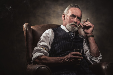 Photo for In chair sitting senior business man with cigar and whisky. Gray hair and beard wearing blue striped gilet and tie. Against brown wall. - Royalty Free Image