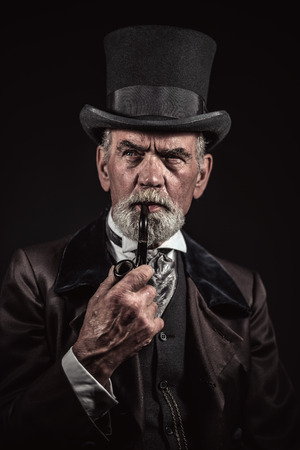 Photo pour Pipe smoking vintage victorian man with black hat and gray hair and beard. Studio shot against dark background. - image libre de droit