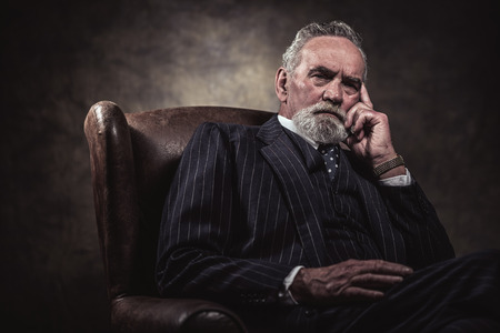 Photo pour In chair sitting characteristic senior business man. Gray hair and beard wearing blue striped suit and tie. Against brown wall. - image libre de droit