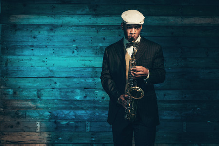 Photo for Vintage african american jazz musician with saxophone in front of old wooden wall. Wearing suit and cap. - Royalty Free Image