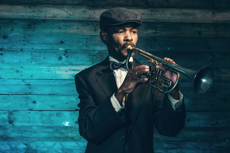 Photo for Vintage african american senior jazz musician with trumpet in front of old wooden wall. Wearing black suit and cap. - Royalty Free Image