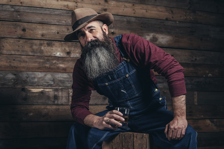 Vintage worker man with long gray beard in jeans dungarees holding whiskey. Sitting on wooden crate in barn.
