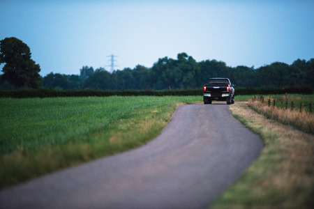 Photo for Pickup truck driving on country road in evening. - Royalty Free Image