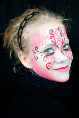 young woman with pink, red and black face paint with a very intense gaze