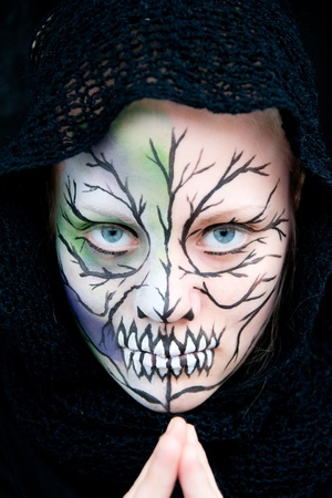 young woman who looks dangerous and crazy with Halloween face painting