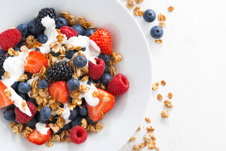 Photo for fresh berries, yogurt and homemade granola for breakfast, close-up, top view, horizontal - Royalty Free Image