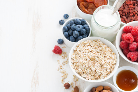 Foto de cereal and various delicious ingredients for breakfast and white wooden background, top view - Imagen libre de derechos