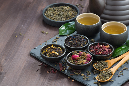 Photo for assortment of fragrant dried teas and green tea on dark wooden table, horizontal - Royalty Free Image
