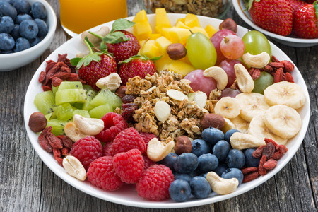 Foto de ingredients for a healthy breakfast - berries, fruit and muesli on wooden table, close-up, horizontal - Imagen libre de derechos