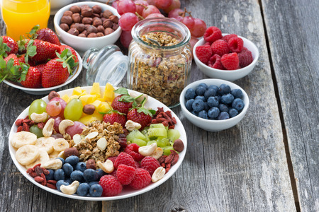 Foto de ingredients for a healthy breakfast - berries, fruit, muesli and wooden background, top view, horizontal - Imagen libre de derechos
