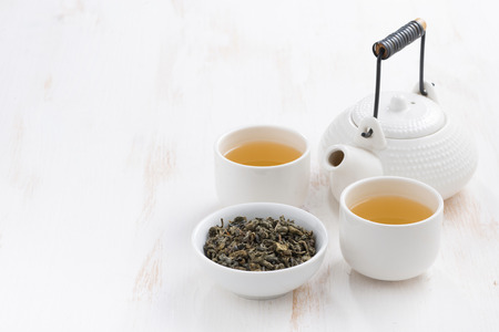 Photo pour teapot and cups of green tea on a white wooden background, horizontal - image libre de droit