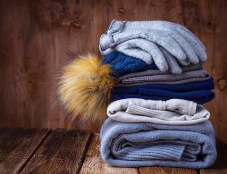 Foto de Stack of warm knitted clothes, sweaters and hat. Selective focus - Imagen libre de derechos