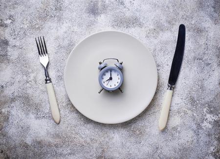 Foto de Grey alarm clock in empty plate. - Imagen libre de derechos