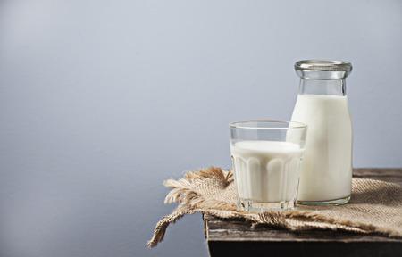 Foto de Milk in a glass bottle on wooden background - Imagen libre de derechos