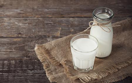 Foto de Milk bottle on wooden background - Imagen libre de derechos