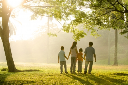 an asian family walking in the park during a beautiful sunrise, backlight
