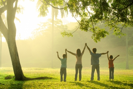 Foto de an asian family jumping in joy in the park during a beautiful sunrise, backlight - Imagen libre de derechos