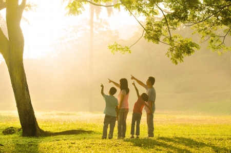 Photo pour an asian family pointing to somewhere during a beautiful sunrise, backlight - image libre de droit