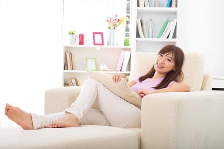 Foto de Beautiful smiling Asian woman with tablet computer. Lying on sofa   - Imagen libre de derechos