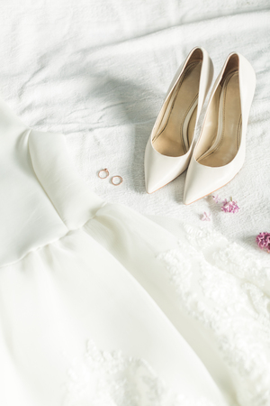 Photo pour Wedding clothes of the bride: dress, shoes and rings - image libre de droit