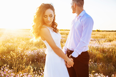 Photo for Beautiful couple in field, lovers or newlywed posing on sunset with perfect sky. - Royalty Free Image