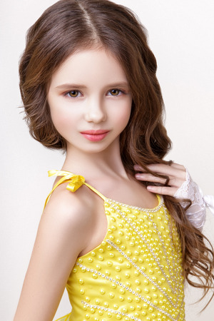 Photo for Little beautiful model girl with long wavy hair dressed in yellow dress posing in studio on a white background - Royalty Free Image