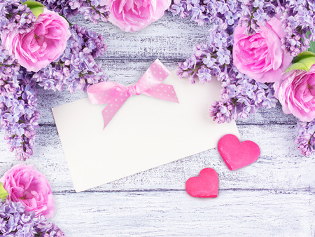 Lilac flowers and roses with paper greeting card for text and two hearts on shabby wooden planks in rustic style. Top view.
