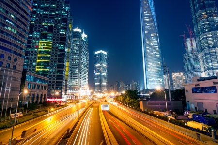 Photo pour light trails on the street with modern building background in shanghai,China - image libre de droit