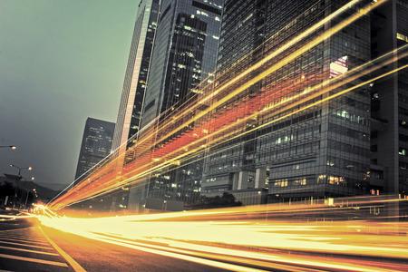 Foto de the light trails on the modern building background in city - Imagen libre de derechos