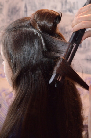 Photo for The hairdresser does a hairstyle on long hair. Bunches of hair and waves with a hair iron - Royalty Free Image
