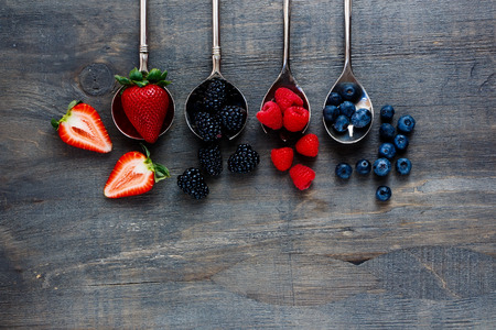 Top view of berries mixed (strawberries, raspberries, blueberries and blackberries) on vintage metal spoons over dark wooden board. Agriculture, Gardening, Harvest Concept. Background with space for text.