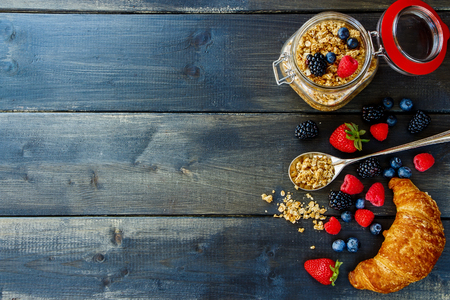 Photo for Top view of homemade granola in glass jar, fresh berries and croissant for breakfast on dark wooden table. Health and diet concept. Background with space for text. - Royalty Free Image