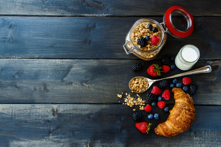 Foto de Croissant, fresh berries, yogurt and homemade granola in glass jar for breakfast on dark wooden table. Health and diet concept. Background with space for text. - Imagen libre de derechos