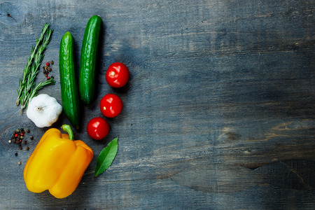 Photo pour Top view of fresh vegetables and spices on dark wooden background with space for text. Vegetarian food, health or cooking concept. - image libre de droit