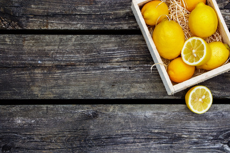 Photo pour Juicy whole lemons and freshly cut half on rustic wooden background with space for text. Top view. - image libre de droit