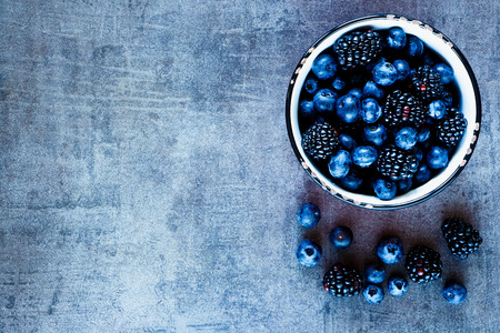 Photo for Organic fresh dark berries in vintage mug over rustic background with space for text, top view. - Royalty Free Image