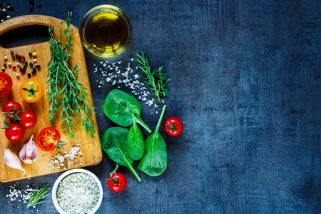 Photo pour Organic vegetarian ingredients, olive oil and seasoning on rustic wooden cutting board over dark vintage background with space for text, top view. - image libre de droit