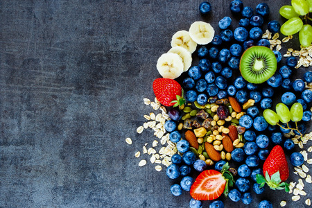 Photo pour Fresh healthy ingredients (oat flakes, green grapes, banana, berries with yogurt and seeds) for breakfast or smoothie on dark vintage background - image libre de droit