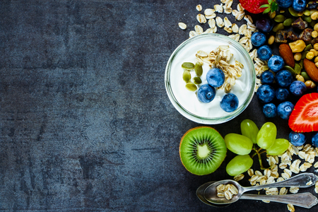 Photo pour Close up of tasty ingredients (oat flakes, green grapes, kiwi, berries with yogurt and seeds) for breakfast or smoothie on dark vintage background - image libre de droit