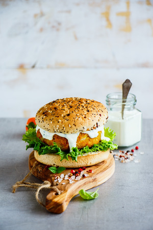 Foto de Freshly made vegan carrot and oats burger, wholegrain buns on wooden board over stone background, selective focus, copy space. - Imagen libre de derechos